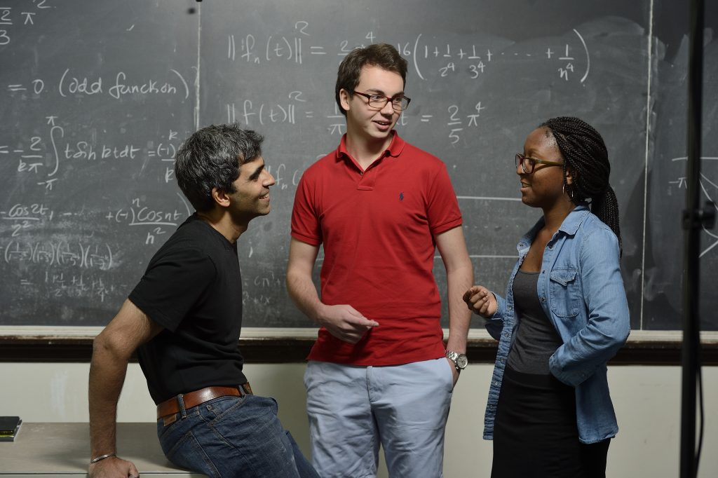 Two JHU students discuss mathematics with a Professor, in front of a board of written formulas.