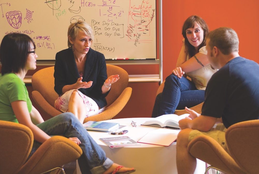 A professor meeting with a group of students.
